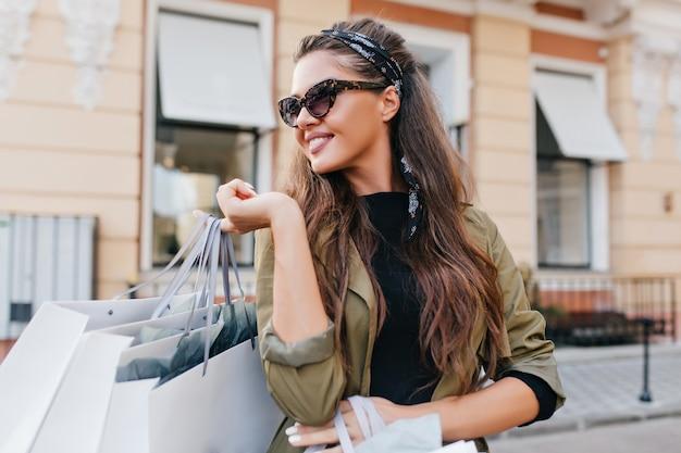 Refinada modelo feminina hispânica com cabelo comprido rindo e olhando para longe, caminhando na rua