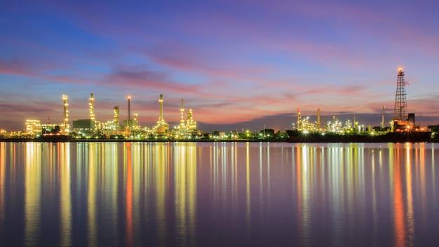 Refinaria de petróleo de panorama ao longo do rio ao entardecer