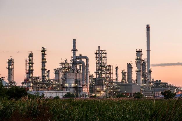 Refinaria de petróleo e coluna de planta e torre da indústria petroquímica em petróleo e gás industrial com céu azul de nuvem ao fundo do nascer do sol