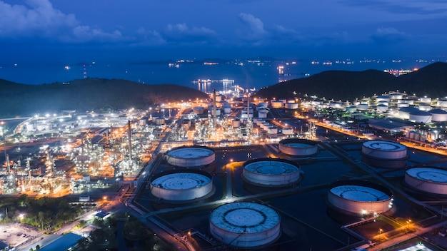 Refinaria de petróleo e indústria petroquímica de gás com área de tubulação de aço de tanques de armazenamento na vista aérea do crepúsculo