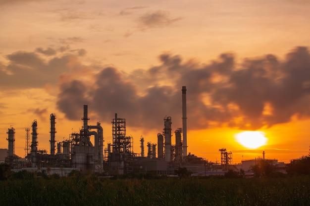 Refinaria de petróleo e planta e coluna de torre da indústria petroquímica em oleoduto industrial de petróleo e gás com nuvens diminuindo o céu vermelho o fundo da manhã