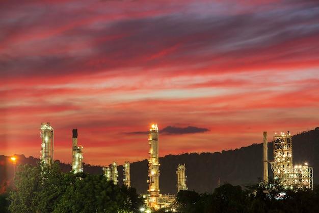 Refinaria de petróleo e planta e coluna de torre da indústria petroquímica na indústria de petróleo e gás com céu vermelho de nuvem e fundo do nascer do sol