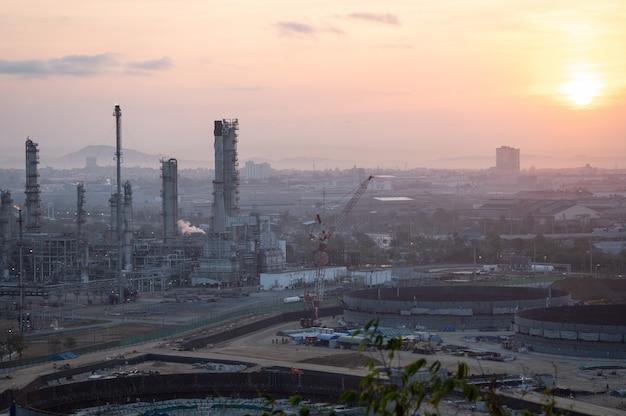 Refinaria de petróleo e tráfego rodoviário ao nascer do sol.