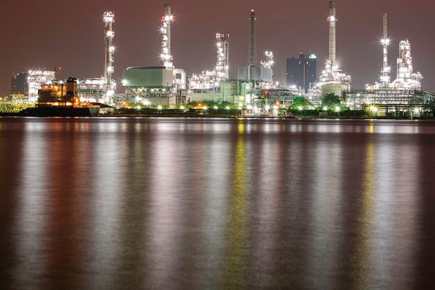 Refinaria de petróleo pela manhã com reflexo na água