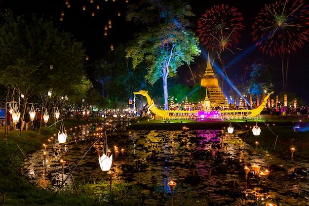 Reflexão bonita do fogo de artifício sobre a cidade histórica surpreendente velha de loy krathong festival sukhothai tailândia do pagode. cidade colorida.