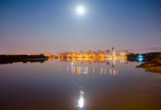 Reflexão da cidade à noite na superfície da água.