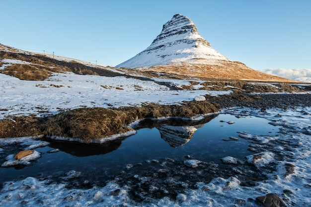 Reflexão da montanha kirkjufell sob céu claro durante a manhã de inverno