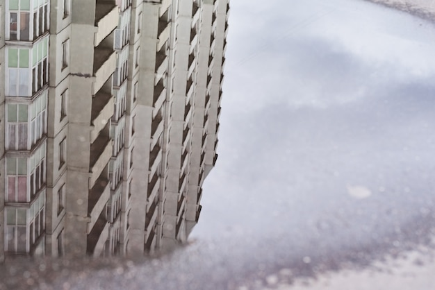 Reflexão de edifícios em poça na rua da cidade