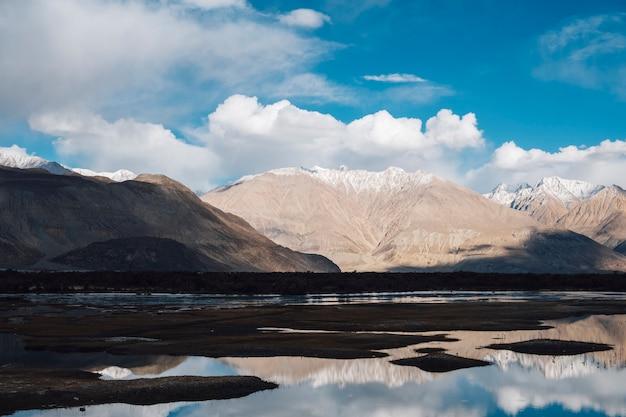 Reflexão de montanha no rio em leh ladakh, índia
