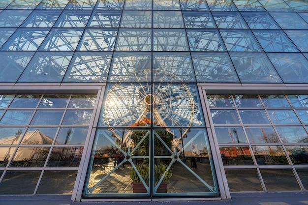 Reflexão de roda-gigante cais da marinha com vidros de janelas na hora por do sol
