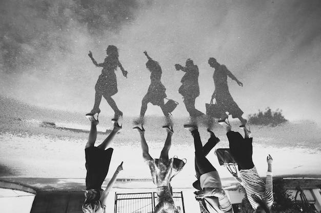 Reflexão de um grupo de pessoas em uma poça na estrada. preto e branco.