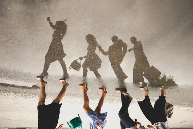 Reflexão de um grupo de pessoas em uma poça na estrada.
