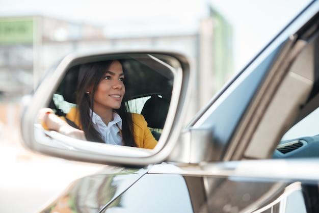 Reflexão de uma jovem mulher comprando um carro novo