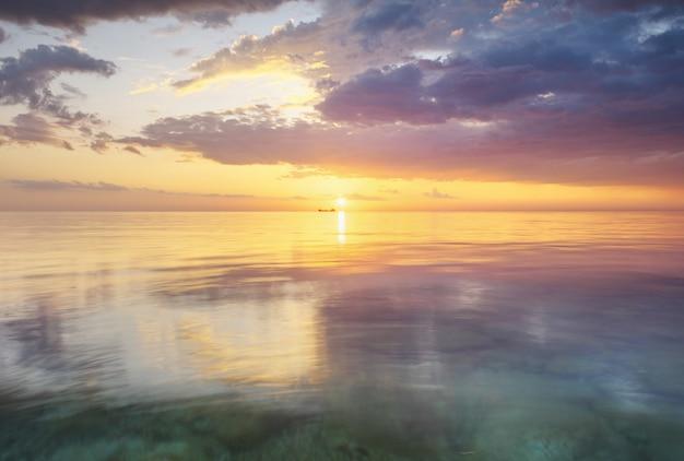 Reflexão do céu e do mar no pôr do sol
