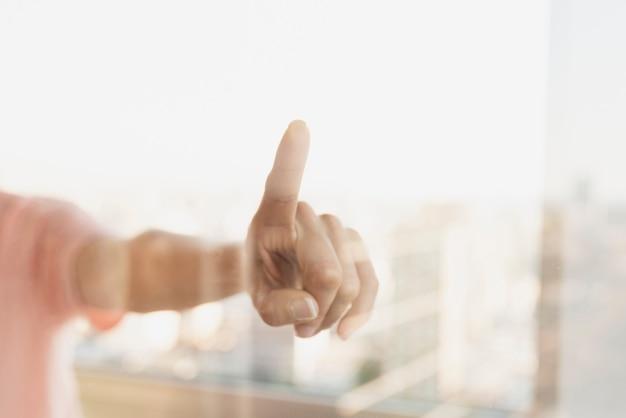 Reflexão do dedo apontando na janela