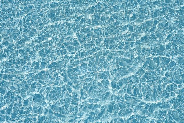 Reflexão e ondas transparentes da textura da água azul da associação