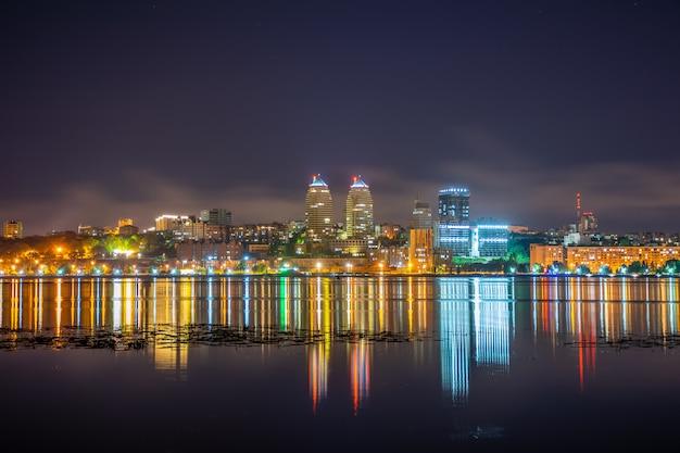 Reflexo da cidade da noite em um rio largo e calmo.