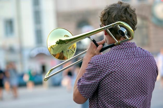 Reflexo da rua no trompete de solo de instrumento. músico masculino toca trombone.