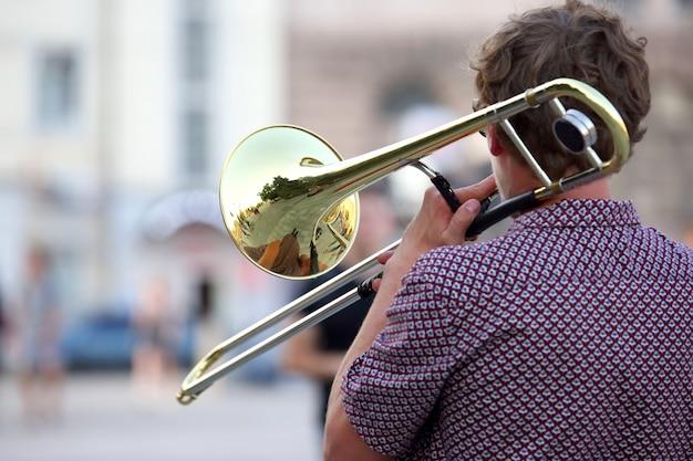 Reflexo da rua no trompete solo de instrumento. um músico masculino toca trombone