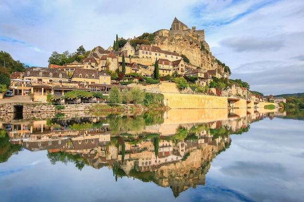 Reflexo da vila de beynac-et-cazenac na água, beynac-et-cazenac é uma vila classificada como uma das mais belas vilas da frança.