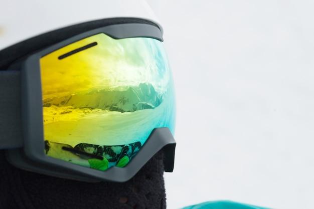 Reflexo das montanhas na máscara de um snowboarder. gudauri, geórgia