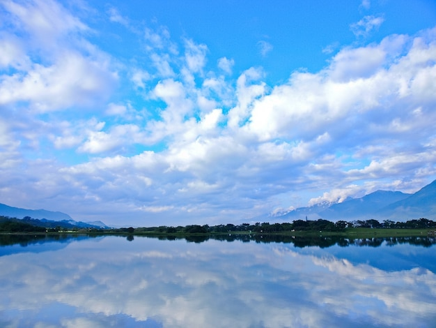 Reflexo de árvores, montanhas e ilhas no lago claro na manhã de domingo