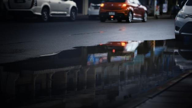 Reflexo de carros embaçados em uma poça na rua da cidade após a forte queda de chuva, foco seletivo. estação chuvosa, fundo de transporte.