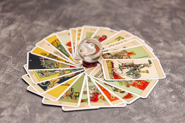 Reflexo de cartas de tarô através da bola mágica na mesa do cartomante
