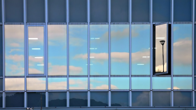 Reflexo de céu nublado na parede de vidro de um edifício moderno