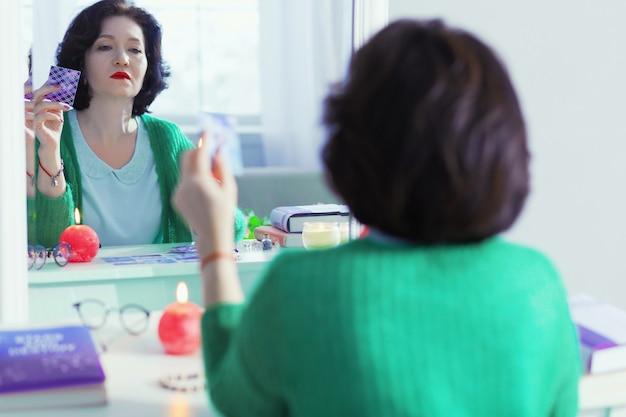 Reflexo de espelho. linda mulher de cabelos escuros olhando para si mesma enquanto furava uma carta de tarô