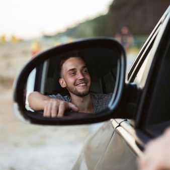 Reflexo de homem no espelho do carro