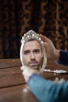 Reflexo de homens de modelo de moda no espelho. retrato de jovem bonito olhando no espelho