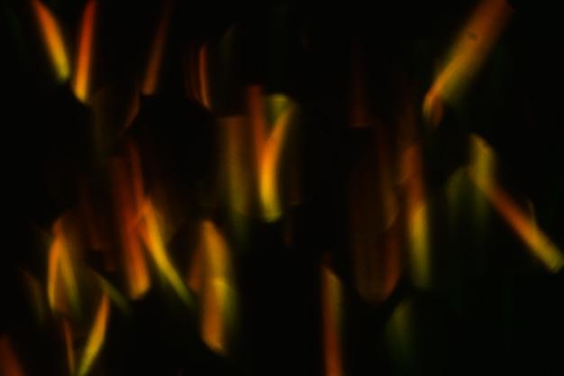 Reflexo de lente abstrato na parede preta. luzes laranja desfocadas bokeh. decoração de papel de parede de natal turva. projeto festivo de círculos brilhantes.