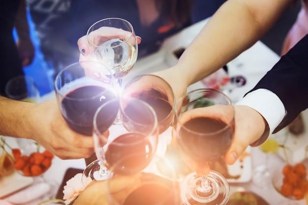 Reflexo de lente curto de mãos masculinas e femininas com copos cheios de vinho acima da mesa do restaurante. brindes e copos tilintando em um jantar. beber vinho em um banquete. festejar um evento
