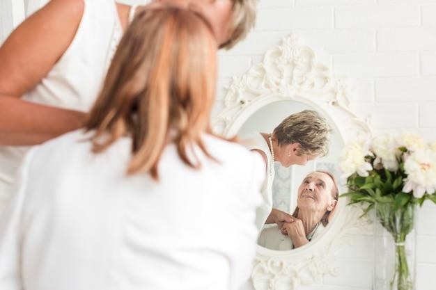 Reflexo de mãe e filha no espelho em casa