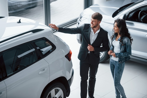 Reflexo de pessoas no vidro. cliente do sexo feminino e empresário barbudo elegante e moderno no salão automóvel
