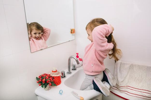 Reflexo de uma garota feliz amarrando o cabelo no espelho