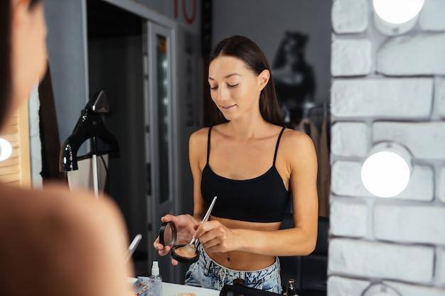 Reflexo de uma jovem e bela mulher aplicando sua maquiagem