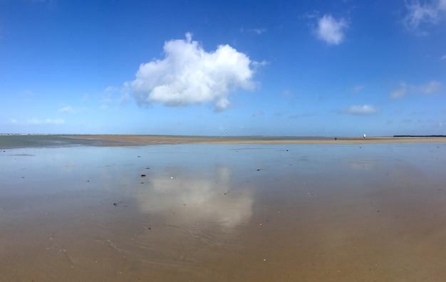 Reflexo de uma nuvem branca em um céu azul na areia úmida de uma praia do oceano atlântico