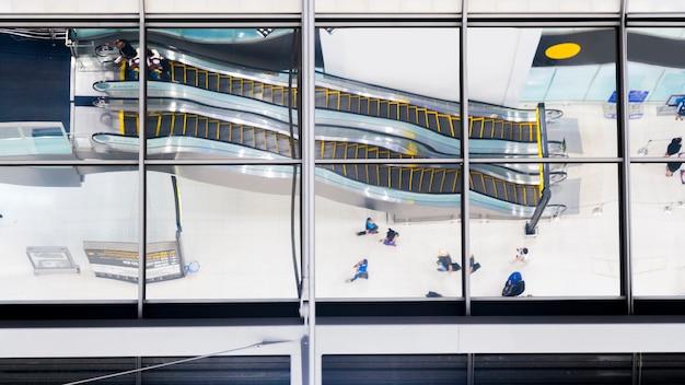 Reflexo de vidro de pessoas de vista superior a pé e sentar escada rolante de escada no aeroporto