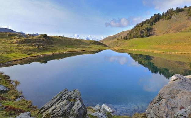 Reflexo do céu na água de um lago de montanha alpina