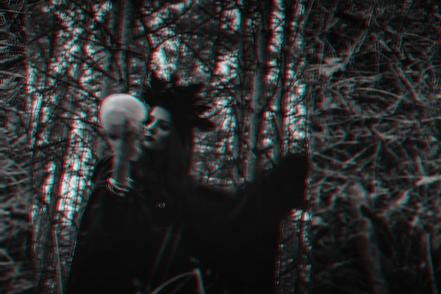Reflexo místico embaçado de uma bruxa negra com uma caveira nas mãos realizando um ritual satânico. preto e branco com efeito de realidade virtual de falha 3d