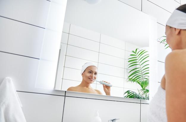Reflexo no espelho de uma jovem bonita e saudável escovando os dentes.