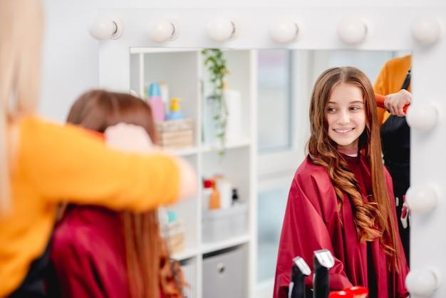 Reflexo no espelho de uma jovem e atraente modelo sorridente com cachos durante o processo de penteado no salão de beleza