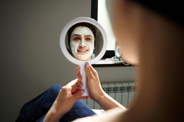Reflexo no espelho de uma jovem sorridente com máscara de alginato no rosto, olhando-se em um pequeno espelho. conceito de cuidados com a pele