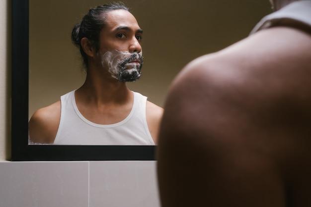 Reflexo no espelho do banheiro de um homem latino com creme de barbear