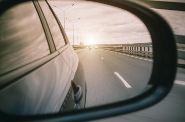 Reflexo no espelho retrovisor do carro e a luz da estrada.