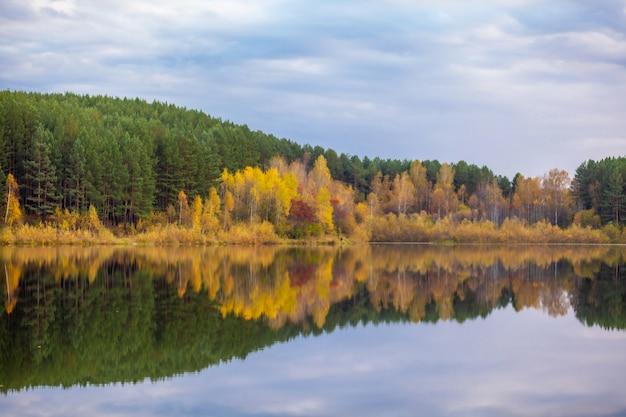 Reflexões de árvore de folhagem colorida na água calma da lagoa em um lindo dia de outono. um lugar tranquilo e bonito para relaxar.