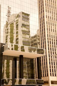 Reflexões de edifício antigo em um edifício de vidro moderno