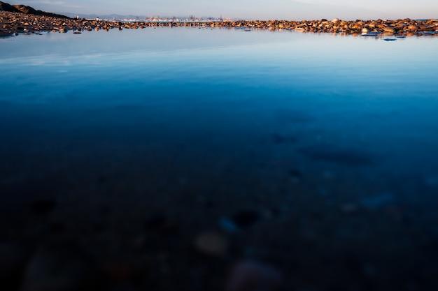 Reflexões em uma poça de água do mar em uma praia, com a cidade
